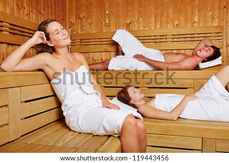 Three young people sitting relaxed in a sauna - stock photo