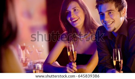 Three young people with champagne glasses at restaurant. Love, party and dating concept.