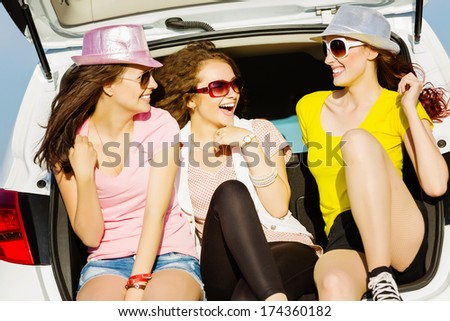 Three young pretty lady sitting in car boot - stock photo