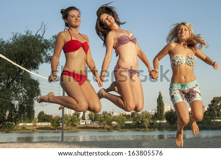 Three young sexy ladies are jumping at volleyball beach  - stock photo