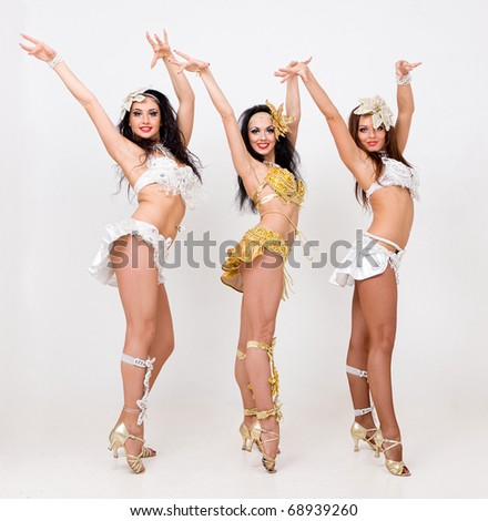 Three young sexy women dancing on a gray background - stock photo