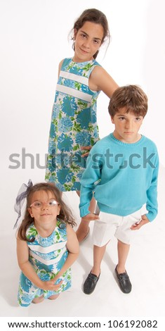 Three young siblings dressed in matching clothes - stock photo
