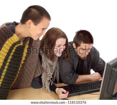 Three young smiling Caucasian people looking to computer