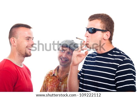 Three young smiling guys smoking hashish joint, isolated on white background. - stock photo