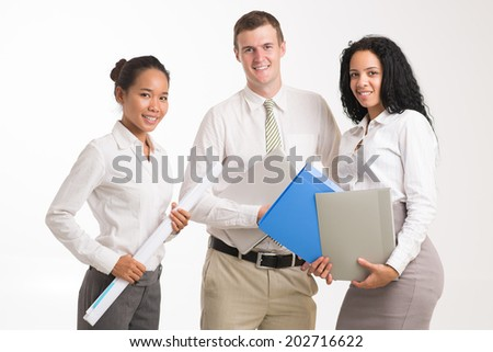 Three young smiling managers with laptop and documents - stock photo