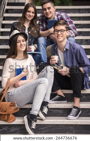 Three young students learning on stairs in college. And looking on camera. - stock photo