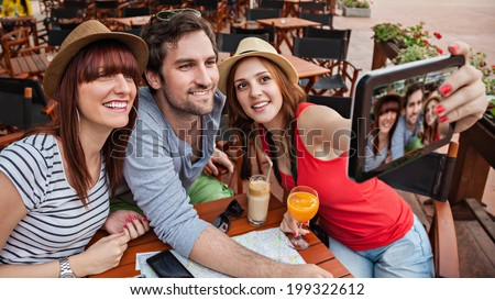 Three Young Tourists In Cafe Taking Selfie. - stock photo