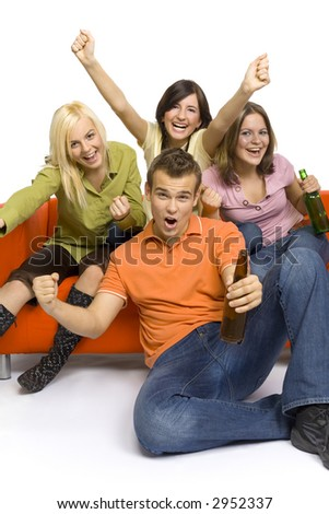 Three young woman and a man are sitting on (and next to) the orange couch. Two of them are holding beer. They're shouting and gesturing. - stock photo