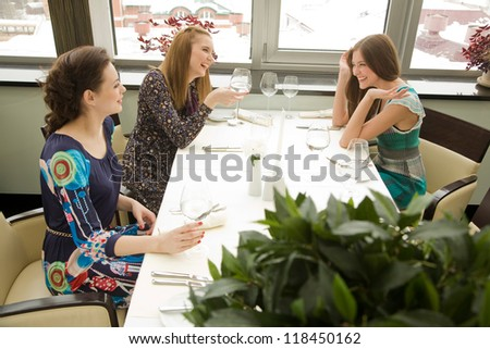 Three young woman are chatting while waiting their order in the restaurant.Selective focus with a plant at the foreground - stock photo