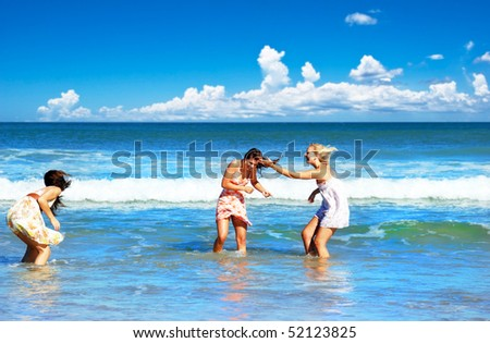 Three young woman having fun in the tropical sea on a summer day