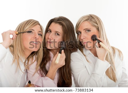 Three young women applying make-up, getting ready to go out - stock photo