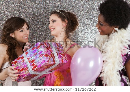 Three young women at a birthday party offering presents and holding balloons against a silver glitter background.