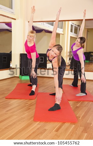 three young women doing stretching exercises in gym - stock photo
