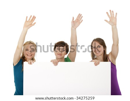 Three young women holding a blank banner, greeting and smiling. - stock photo