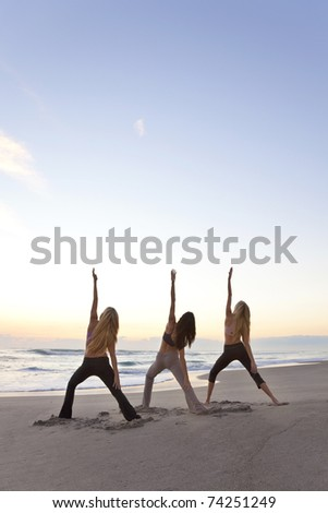 Three young women in a warrior position practicing yoga on a beach at sunrise or sunset - stock photo