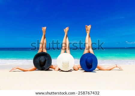 Three young women in straw hats lying on a tropical beach, stretching up slender legs. Blue sea in the background. Summer vacation concept. - stock photo
