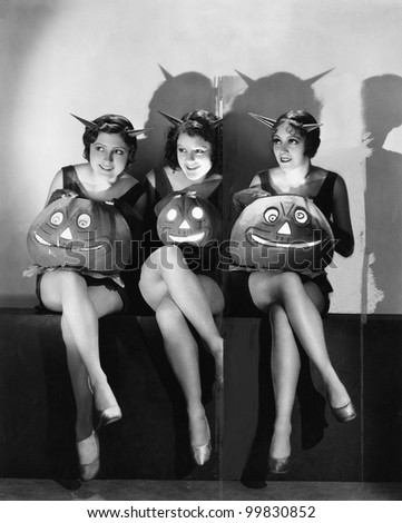 Three young women sitting and holding Jack O' Lanterns on their laps - stock photo