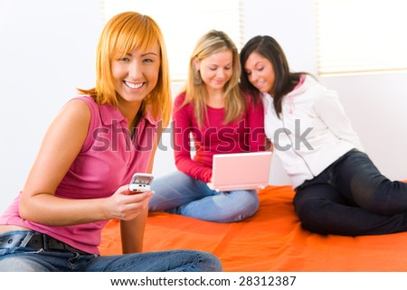 Three young women sitting on bed. Two of them doing something on laptop. Focused on  red-haired girl with cellphone.