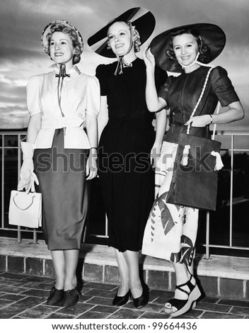 Three young women standing side by side and smiling - stock photo