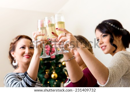 Three young women toasting with champagne - stock photo