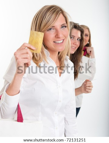 Three young women with happy expressions with credit cards holding lots of shopping bags - stock photo