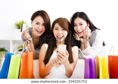 three young women with shopping bags and looking at smart phone - stock photo