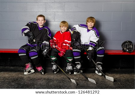 Three Youth Boys Hockey Players Pose in Dressing Room in their equipment