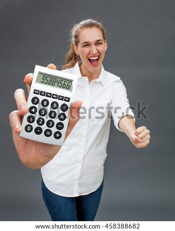 thrilled beautiful young woman laughing for successful ambition, winning the jackpot in holding a symbolic calculator in the foreground - stock photo