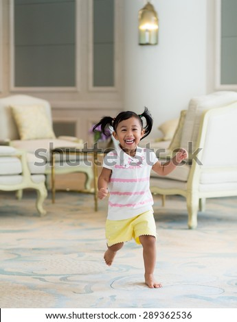 Thrilled girl running at home - stock photo