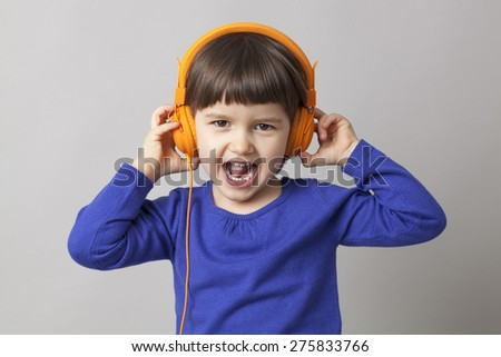thrilled young child enjoying rhythms in listening to music on headphones - stock photo