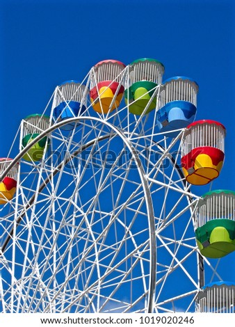 Thrilling Exhilarating Ferris Wheel with Bold Bright Coloured Passenger Capsules.