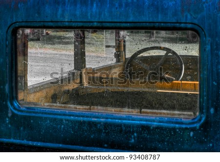 Through the Back Window - view of interior of old blue truck with wooden interior - stock photo