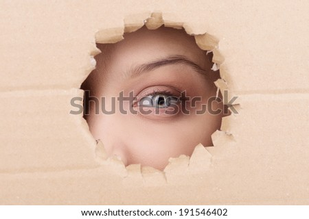 Through the looking hole. Closeup of an eye looking through a hole in a piece of cardboard - stock photo