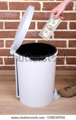 Throwing away your money on brick wall background - stock photo