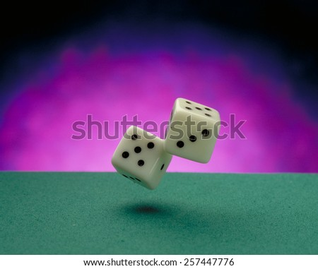 Throwing dices on a green casino felt. - stock photo