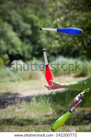 throwing juggling clubs outdoor  - stock photo