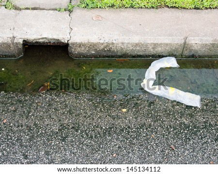 Thrown plastic bags affect dirty water drains - stock photo