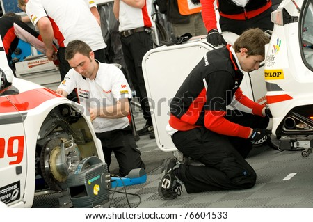 THRUXTON, UNITED KINGDOM - MAY 1: Mechanics from the Honda team working on the race winning Civics at the British Touring Car Championships on May 1, 2011 at Thruxton, UK