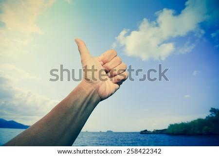 Thumb point to the blue sky in the mood of retro photography, relaxing symbol. - stock photo
