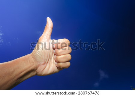 Thumb point to the deep blue sky, success and relaxing symbol.