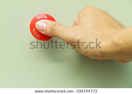 Thumb touch on red emergency stop switch on control panel for machine control in emergency case - stock photo
