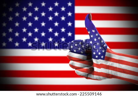 Thumb up for USA over national flag in background - stock photo
