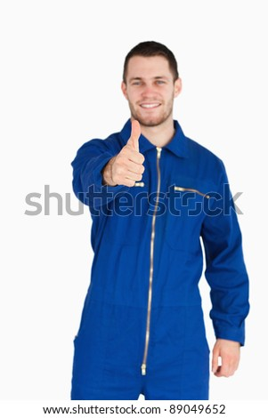 Thumb up given by smiling young mechanic in boiler suit against a white background - stock photo