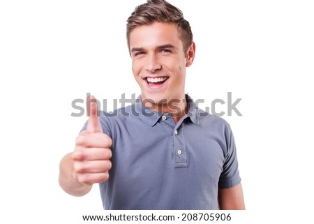 Thumb up! Happy young man looking at camera and showing his thumb up while standing isolated on white background - stock photo