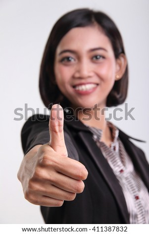 Thumb up of an attractive Asian corporate woman, close up portrait against isolated background - stock photo