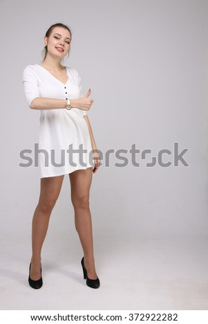 Thumb up. Woman on gray background. Female model. - stock photo