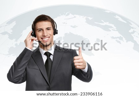 Thumbing up businessman puts earphones with microphone, successful negotiation - stock photo