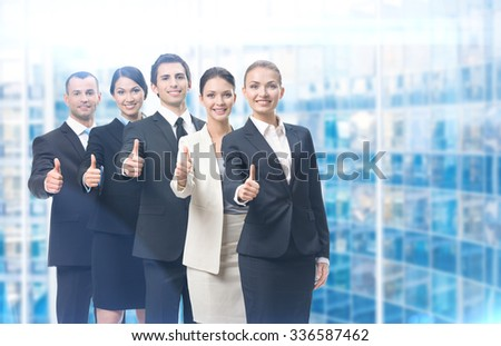 Thumbing up group of business people, blue background. Concept of teamwork and cooperation