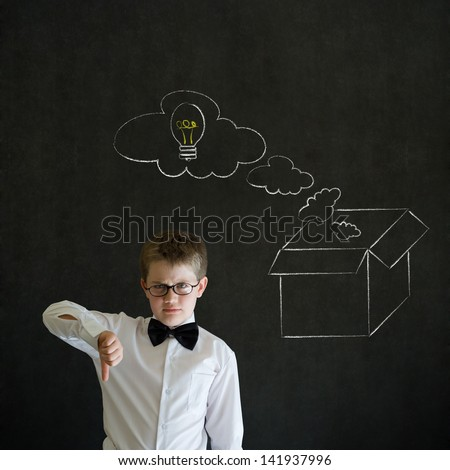 Thumbs down boy dressed up as business man with chalk thinking out the box concept  on blackboard background - stock photo
