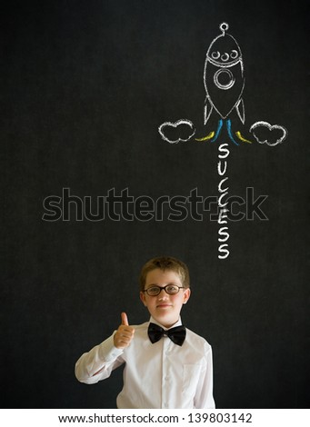 Thumbs up boy dressed up as business man with chalk success rocket on blackboard background - stock photo